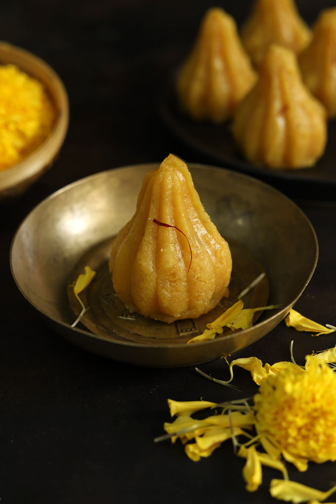 close up side shot of modak on a brass serving bowl