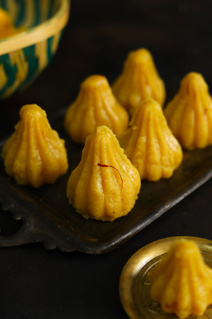 side shot of khoya modak arranged on a black serving tray