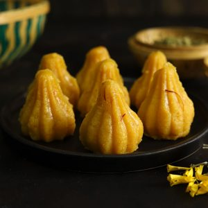 close up side shot of mawa modak on a black platter