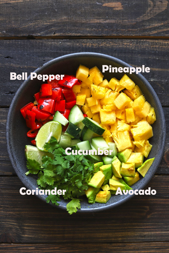 aerial shot of ingredients in a pineapple salsa in a black ceramic bowl.