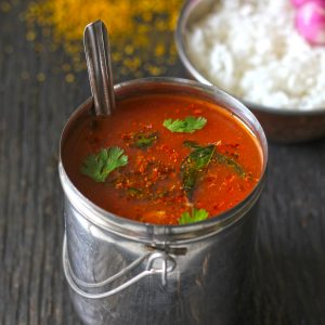 side shot of tomato garlic rasam in a stainless steel container