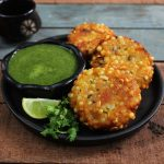 side shot of sabudana vada arranged on a black serving plate with green chutney in a bowl