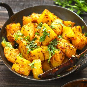 side close up shot of aloo gutuk in a cast iron skillet
