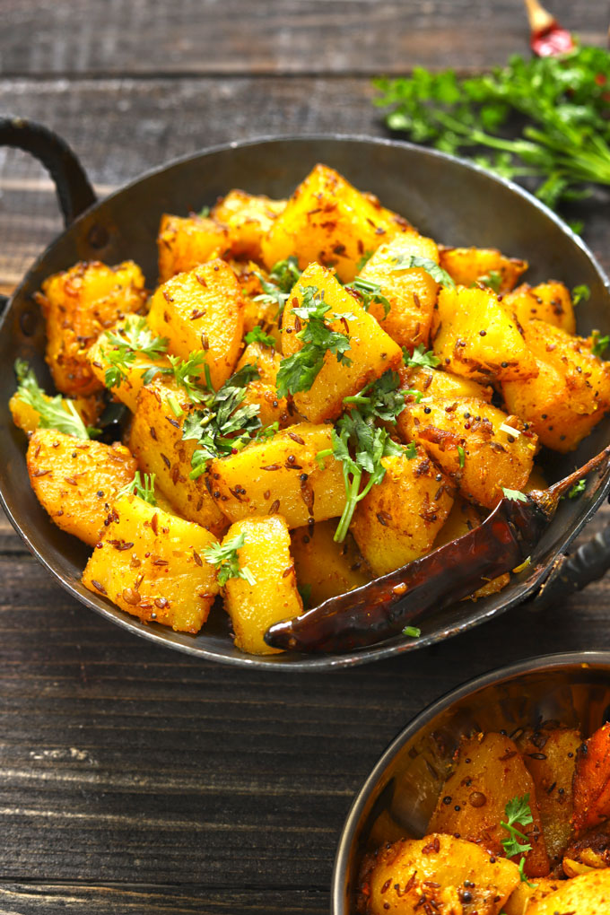 side shot of aloo gutuk in a cast iron skillet