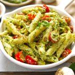 side close up shot of basil pesto pasta in a white pan