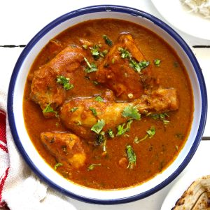 aerial shot of chicken curry in a white serving bowl