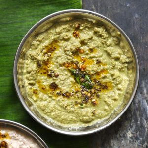 aerial shot of green coconut chutney in a steel bowl