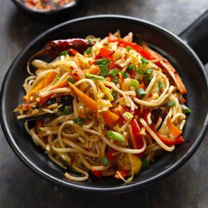 side close up shot of chilli garlic noodles in a black serving bowl