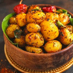 side shot of Indian masala potato roast in a wooden bowl