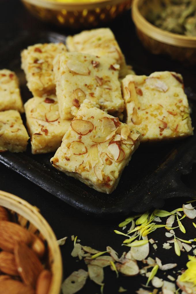 side close up shot of mawa barfi arranged on a black tray