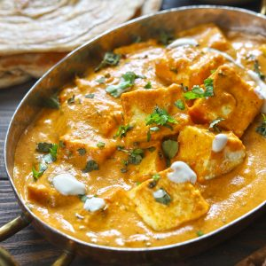 side close up shot of paneer makhani in a copper serveware