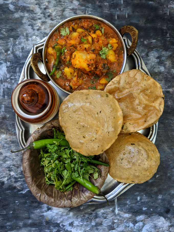 aerial shot of aloo ki sabzi and poori in a plate