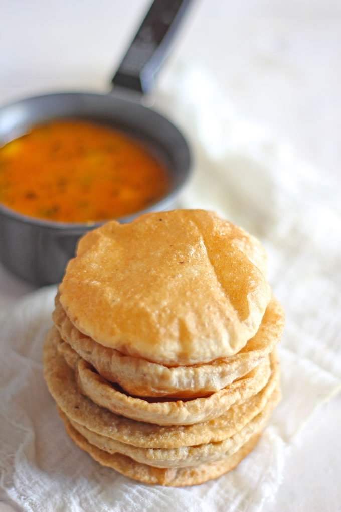 side close up shot of stacked poori on a white background
