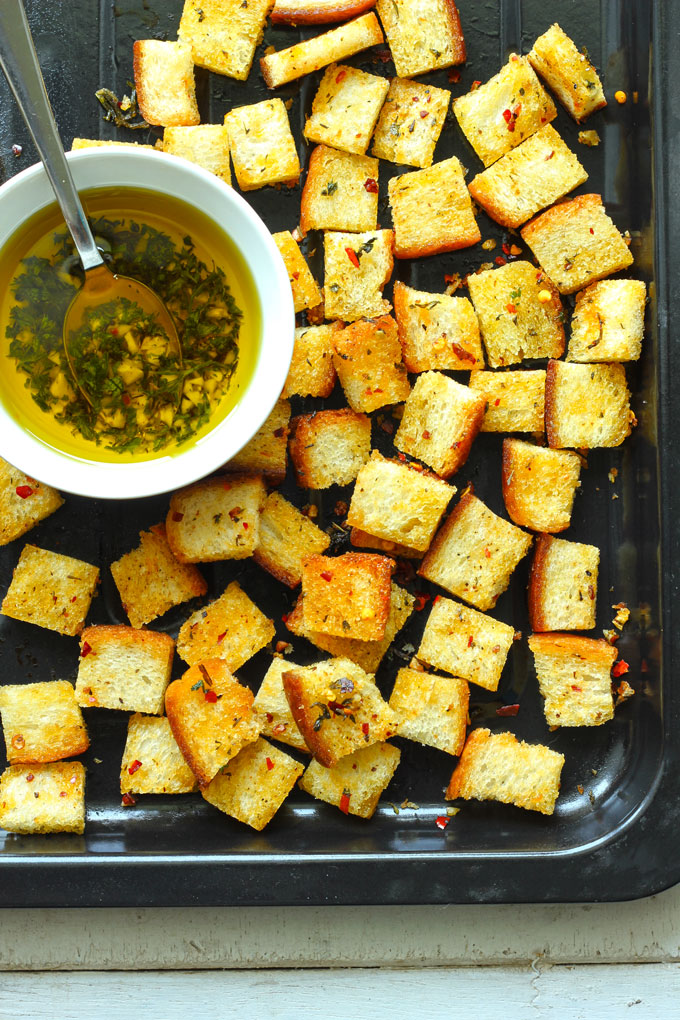 aerial shot of bread croutons on a black baking tray with a bowl of olive oil