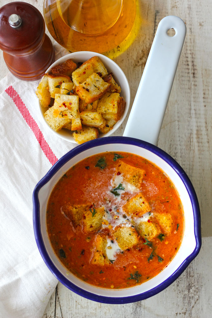 aerial shot of a tomato soup with bread croutons on a white saucepan