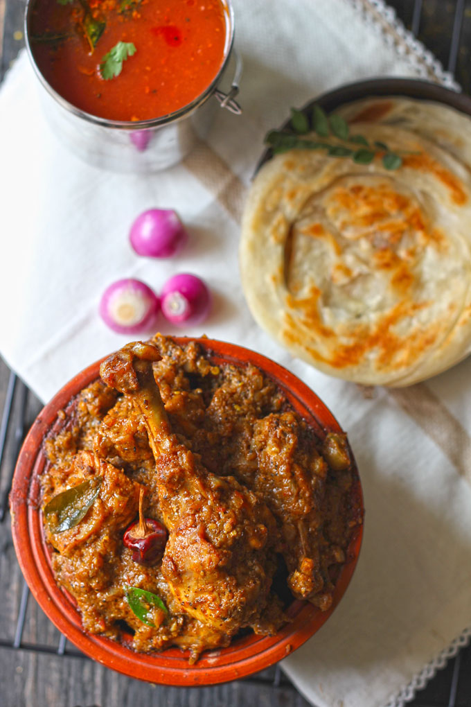 aerial shot of Chettinad chicken in an earthen serving bowl with parotta and tomato rasamv