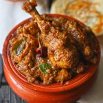 side close up shot of Chettinad chicken masala in a traditional earthen serveware