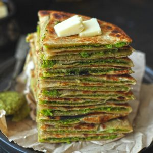 side close up shot of matar paratha stacked on a black plate topped with butter