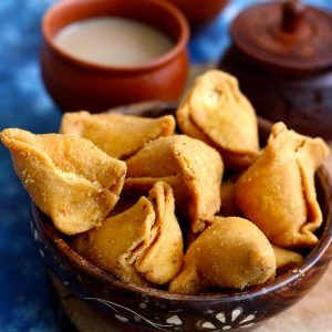 side close up shot of moong dal samosa stacked on a wooden bowl