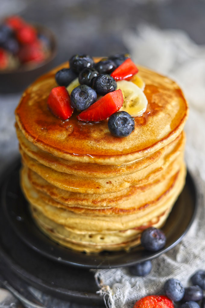 side shot of healthy pancakes stacked on a plate topped with fresh berries