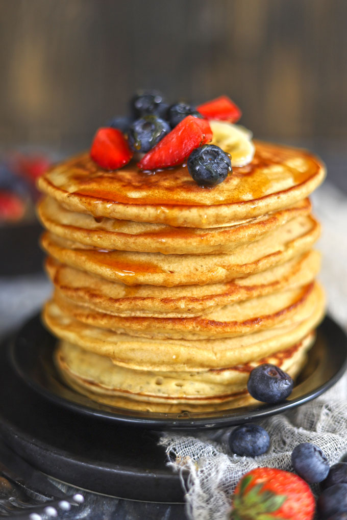 side shot of whole wheat pancakes stacked on a plate
