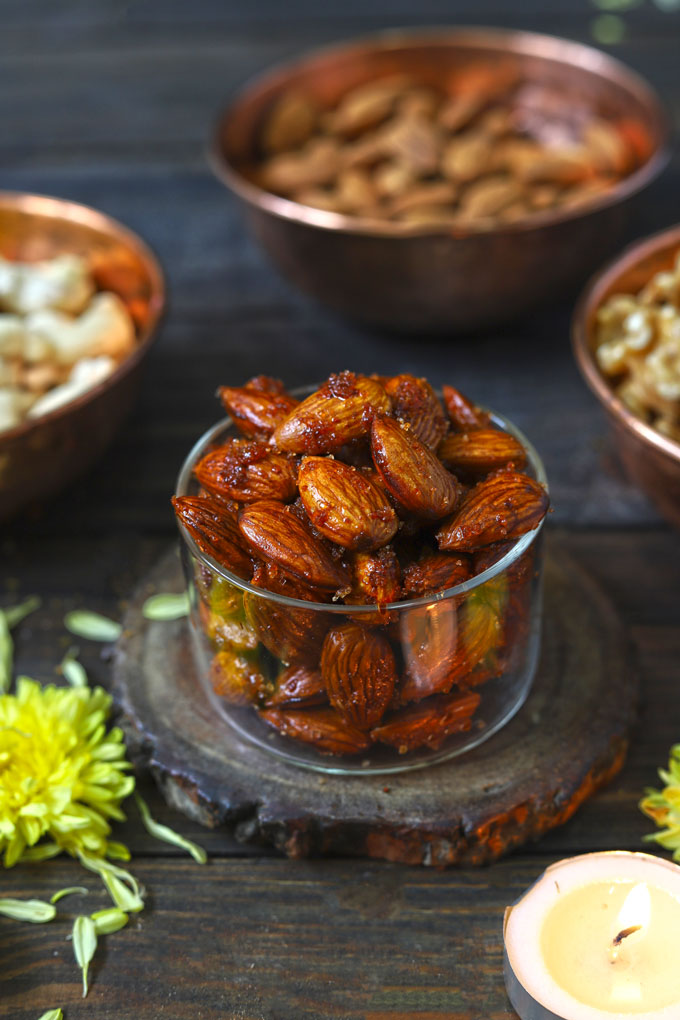 side close up shot of honey spiced almonds in a glass bowl