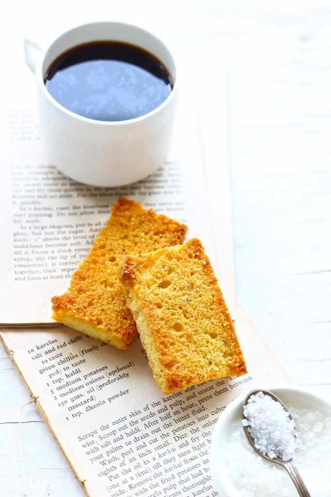 side shot of two pieces of cake rusk stacked on a white surface with a cup of coffee