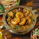 side shot of Chettinad prawn curry served in a tradtional serveware