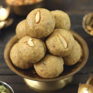 side shot of atta ladoo stacked on a golden platter