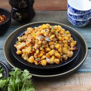 side shot of crispy corn stacked on a black plate