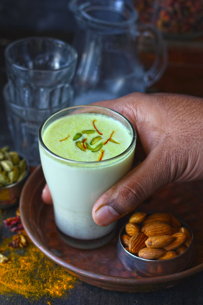 side shot of khas khas doodh in a glass with a hand holding it.