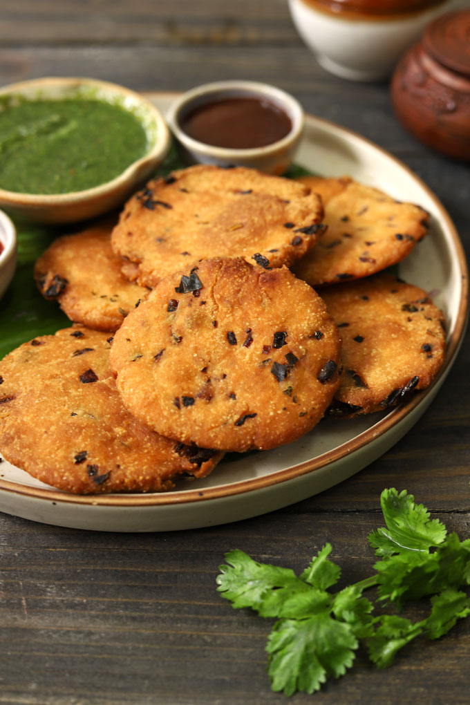 side close up shot of maddur vada stacked on a ceramic plate