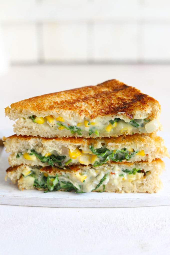 side shot of grilled spinach corn sandwich stacked on a white board