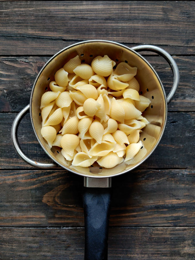 aerial shot of boiled shell pasta on a metal colander