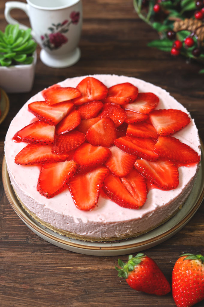 side close up shot of no bake strawberry cheesecake on a round platter