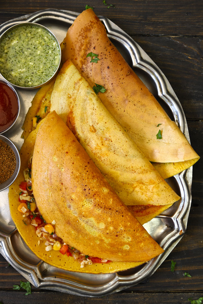 aerial shot of stuffed besan chilla arranged on a steel platter with tomato ketchup and chutney