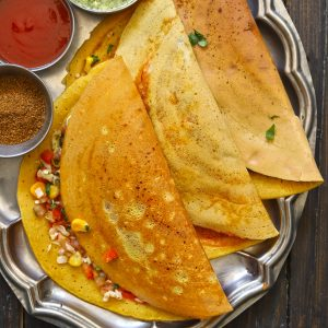 aerial shot of besan ka chilla stacked on a steel platter