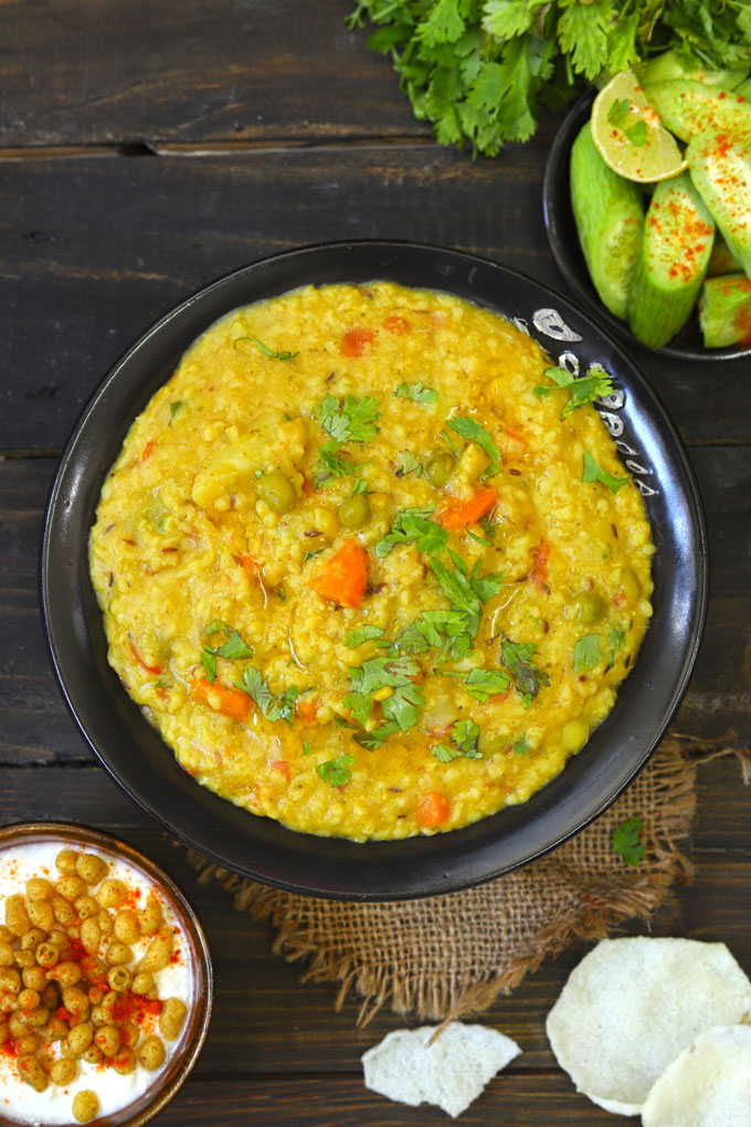 aerial shot of vegetable daliya khichdi in a black serving bowl