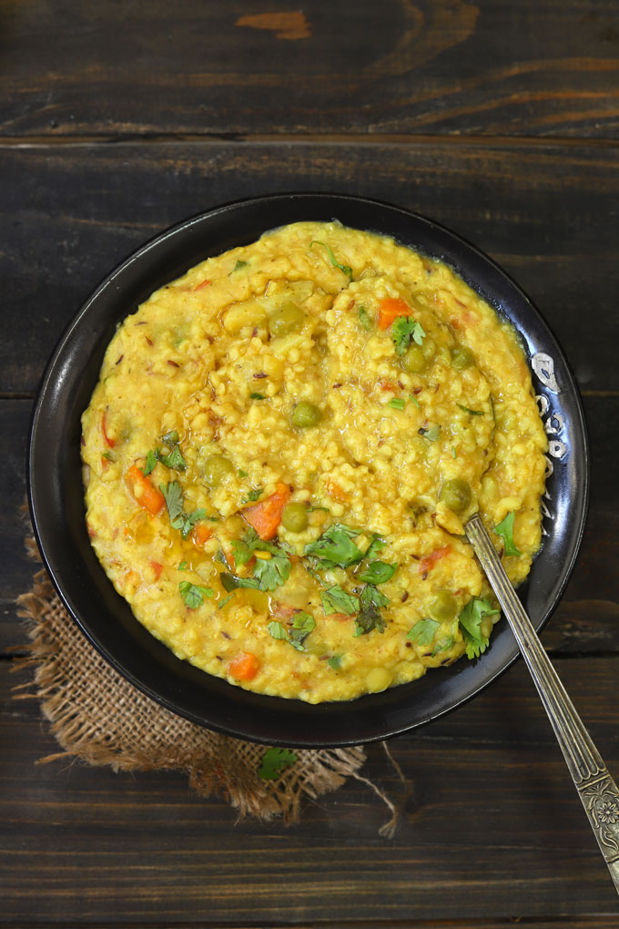 aerial shot of daliya khichdi in a black serving bowl with a serving spoon