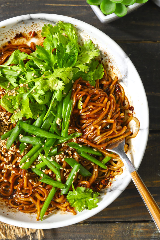 aerial close up shot of chili oil noodles in a bowl with fork and lot of fresh greens