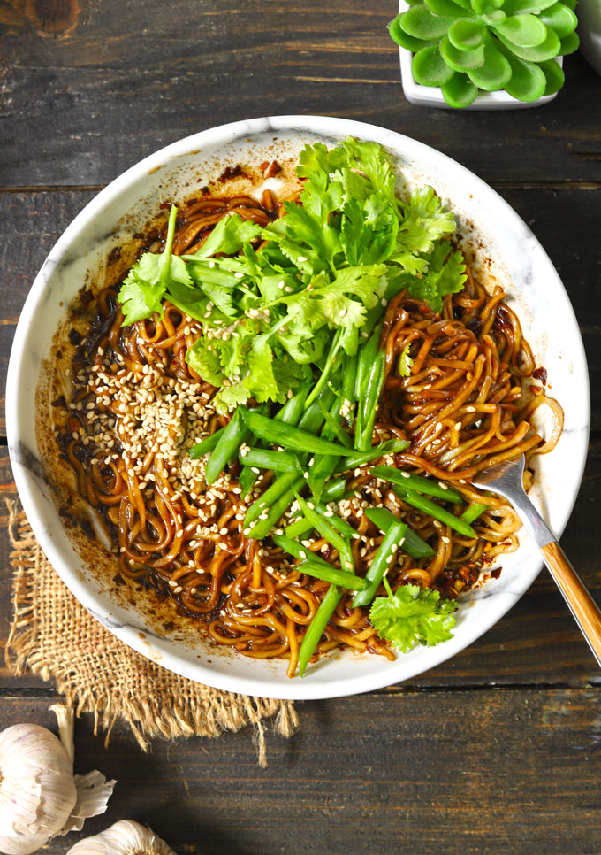 aerial shot of chilli oil noodles in a bowl in a white bowl with fork