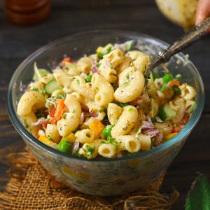 side shot of pasta salad in a bowl with a serving spoon