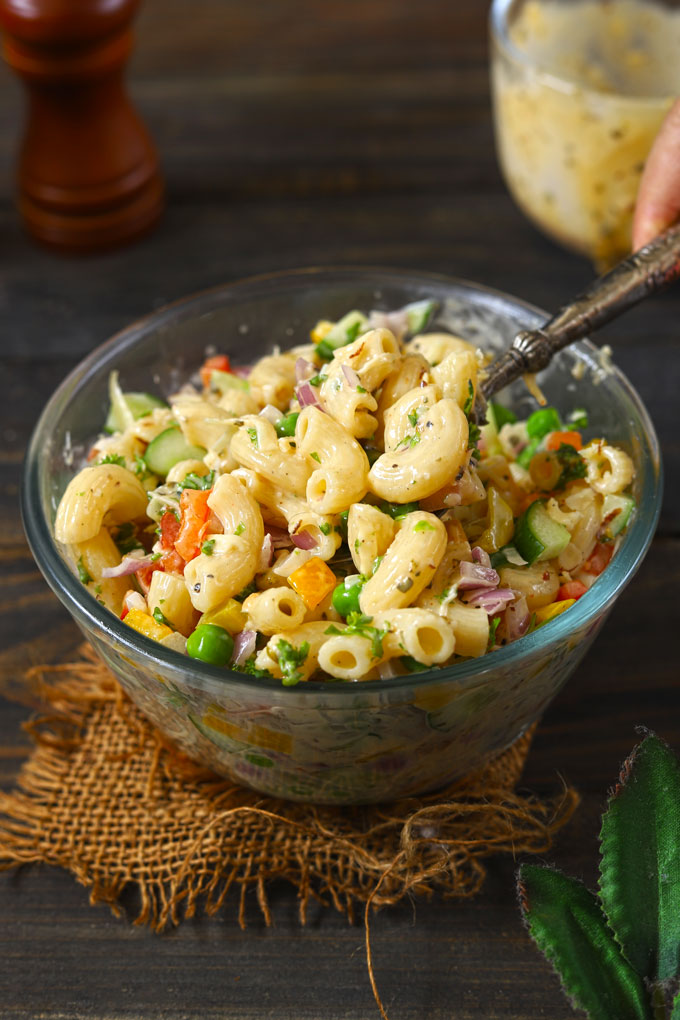 side shot of macaroni salad in a bowl with a serving spoon