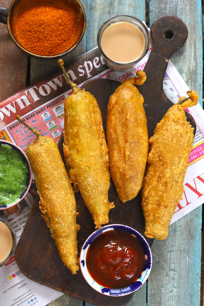 aerial shot of chilli bajji stacked on a brown wooden platter with tea, and chutney