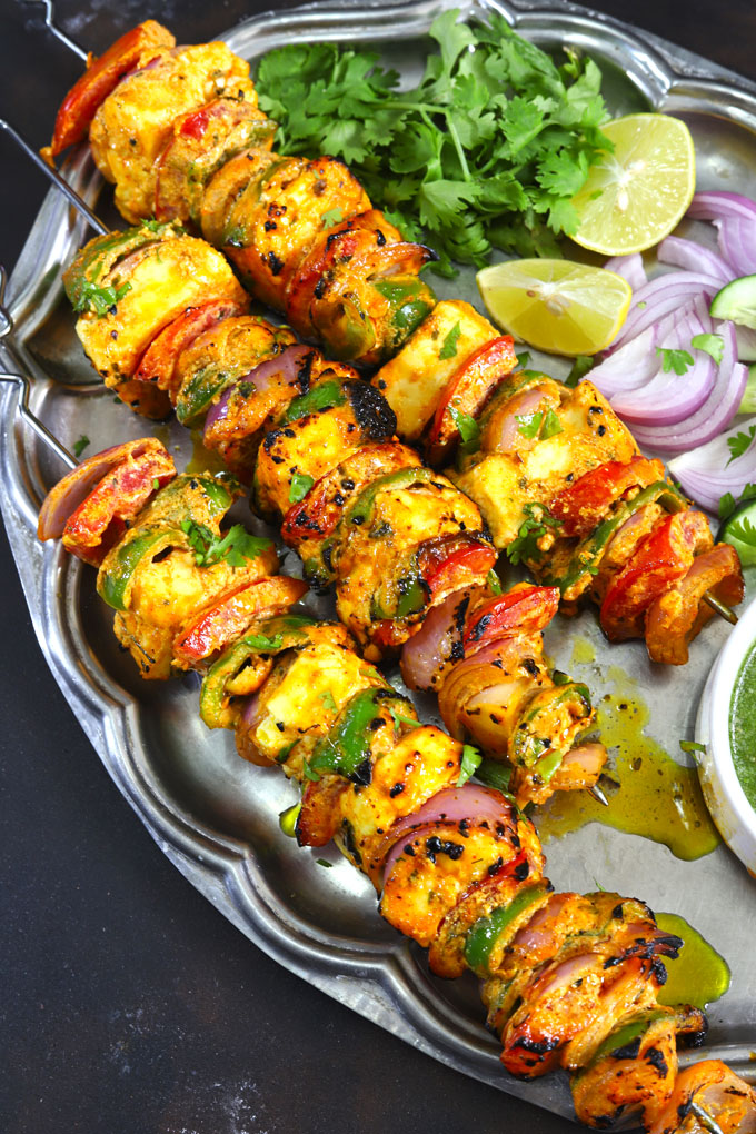 aerial shot paneer tikka skewers stacked on a vintage platter with green chutney and salad