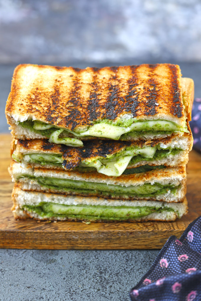 side shot of sliced cheese chutney sandwich stacked on a wooden platter